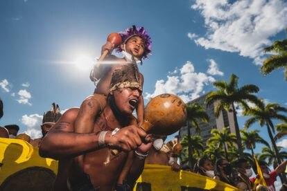 Indígena carrega no ombro uma criança durante a marcha até o Supremo nesta quarta-feira 1.