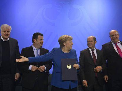 A chanceler alemã, Angela Merkel, mostra o documento assinado por vários ministros, empresários e sindicalistas para acelerar a entrada de trabalhadores qualificados na Alemanha, depois da reunião sobre o tema em Berlim.