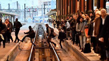 Passageiros cruzam as vias do trem em uma estação de Paris (França).