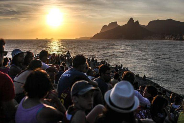 Pessoas observam o pôr do sol na pedra do Arpoador, no Rio de Janeiro.