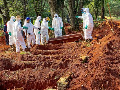 Funcionários do cemitério da Vila Formosa, em São Paulo, enterram vítima da Covid-19.