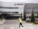 A worker walks at a Boeing production plant Tuesday, April 21, 2020, in Everett, Wash. Boeing this week is restarting production of commercial airplanes in the Seattle area, putting about 27,000 people back to work after operations were halted because of the coronavirus. (AP Photo/Elaine Thompson)