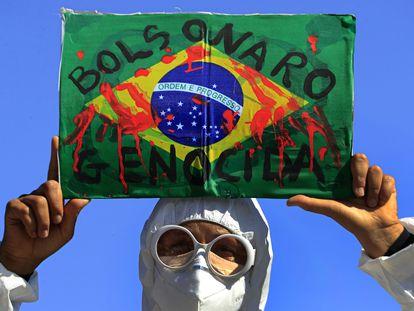 """Manifestante levanta bandeira do Brasil com a inscrição """"Bolsonaro genocida"""" em protesto em Brasília, na quarta."""