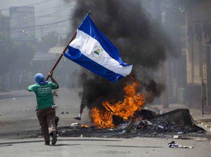 Um jovem corre com uma bandeira em Masaya (Nicarágua) durante um protesto em 2018.