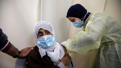 Uma mulher recebe uma dose de vacina contra a covid-19 na Cisjordânia, em 25 de março.
