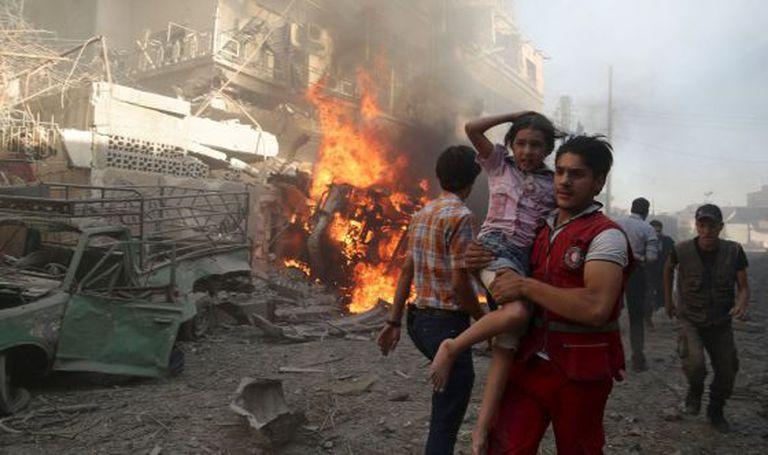 Equipes de socorro resgatam civis depois de um bombardeio na periferia de Damasco.