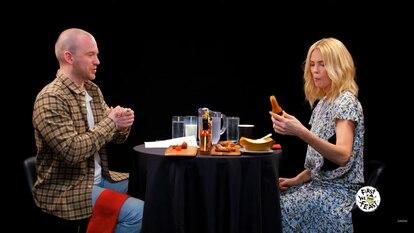 O apresentador Sean Evans com Charlize Theron durante uma edição do programa 'Hot Ones'. No vídeo, um compilado de reações de celebridades.