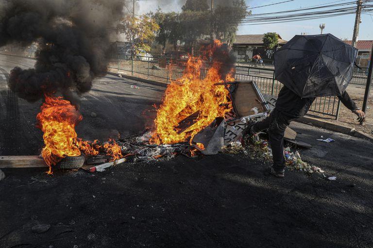 Manifestante chuta os destroços de uma barricada em chamas durante um protesto no bairro de Cerrillos, em Santiago, na sexta-feira, 22 de maio.