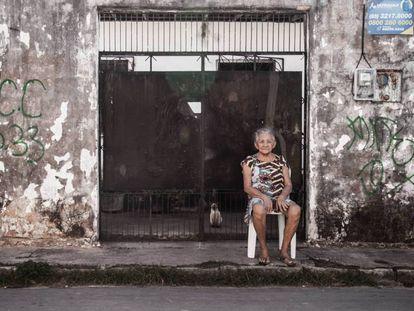 Moradora do bairro do Pirambu, em Fortaleza, ao lado de pichação do PCC.