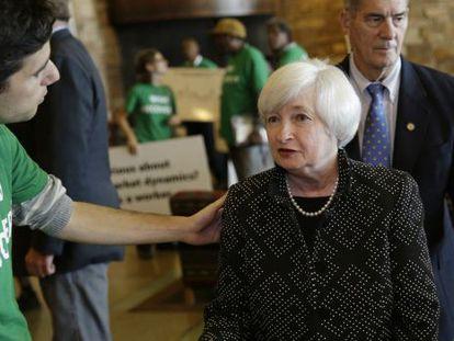 Janet Yellen, presidenta da Reserva Federal, fala com um manifestante.