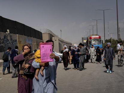 Um homem mostra seus documentos no aeroporto de Cabul.