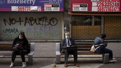 Pessoas sentadas diante de lojas fechadas, em 2 de setembro, em Santiago.
