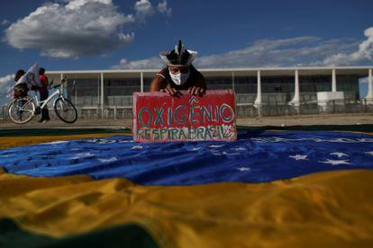 """Um manifestante segura uma faixa que diz """"Oxigênio respira Brasil"""" durante um protesto contra o presidente Jair Bolsonaro em Brasília."""
