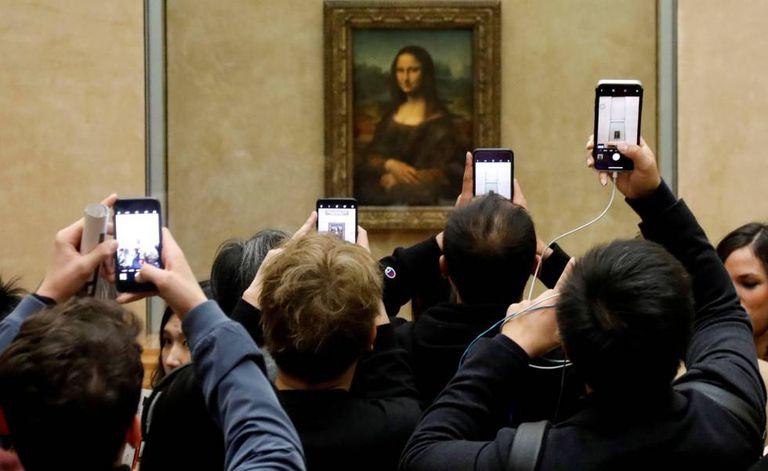 Visitantes do Louvre tiram fotos da 'Mona Lisa', em 3 de dezembro.