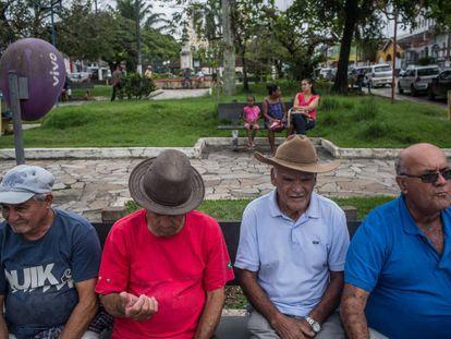 Quatro homens descansam na praça central de Eldorado.