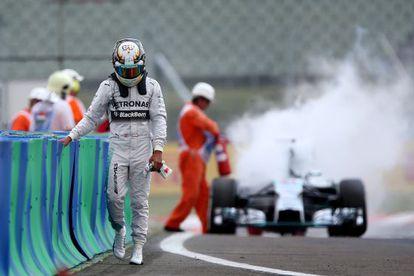 Hamilton afasta-se de seu carro, incendiado.