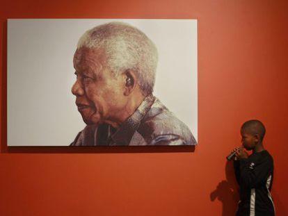 Menino diante foto de Mandela, exposta na sua fundação.