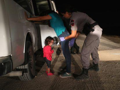 Menina hondurenha chora enquanto sua mãe é revistada pela patrulha fronteiriça em McAllen (Texas), em 2018.