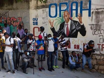 Um grupo de jornalistas se reúne em frente a um mural que mostra o presidente Jovenel Moïse perto da sua residência, onde ele foi assassinado a tiros na madrugada desta quarta-feira, 7 de julho.