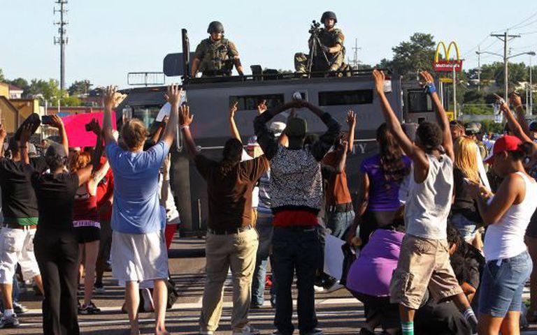Manifestantes diante de um veículo blindado em Ferguson.