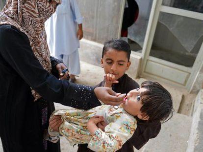 Uma trabalhadora paquistanesa vacina uma criança no Paquistão.