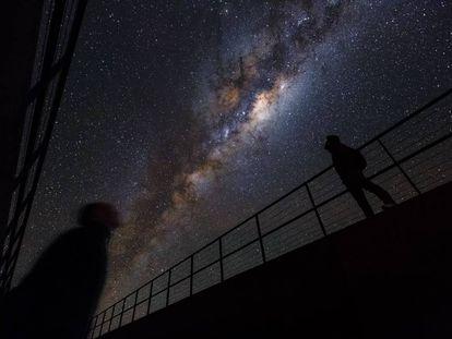 Duas pessoas observam a Via Láctea no monte Paranal (Chile).