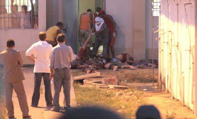 Detentos retiram corpos de presídio durante rebelião de 2008.