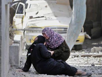 Duas mulheres choram ante os escombros de sua casa em Gaza. (AP)