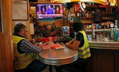 Dois coletes amarelos ouvem Philippe na televisão na quarta-feira, em um bar em Paris.