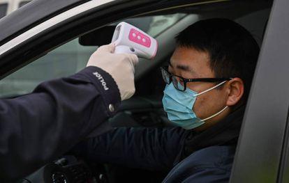 Policial mede a temperatura de motorista em Wuhan, epicentro do surto do coronavírus na China.