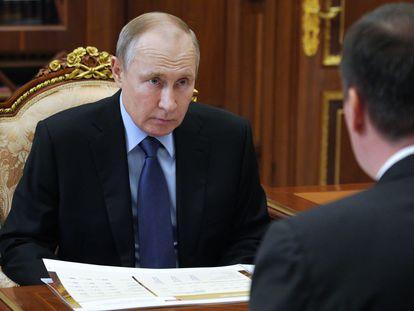 O presidente russo, Vladimir Putin, conversa com o ministro de Agricultura, Dmitri Patrushev, no Kremlin, em Moscou, nesta segunda-feira.