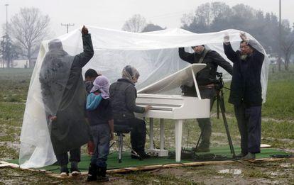 O artista Ai Weiwei (à direita) assiste à apresentação de piano da síria Nour Al Khizam no campo de refugiados situado na fronteira da Grécia com a Macedônia em 12 de março.