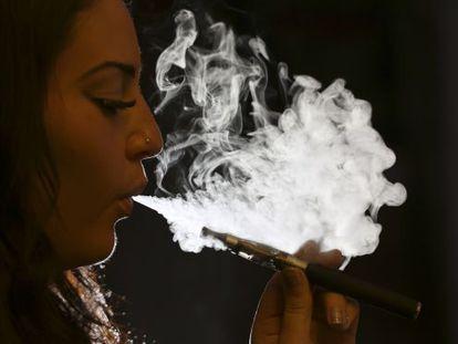 Uma mulher fuma um cigarro eletrônico