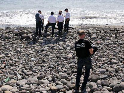 Policiais inspecionam um objeto metálico encontrado na praia de Saint-Denis, na ilha Reunião, em 2 de agosto.