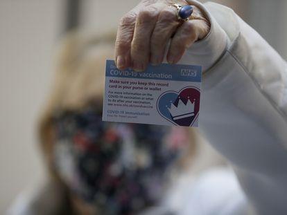 A britânica Lyn Wheeler mostra seu cartão de vacinação após receber a vacina contra covid-19 da Pfizer/BioNTech em um hospital de Londres.