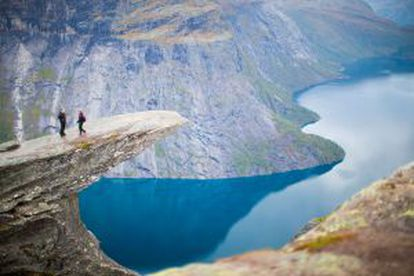 Um casal em Trolltunga, um vertiginoso mirante natural sobre o lago Ringedalsvatneten, em Skjeggedal (Noruega).