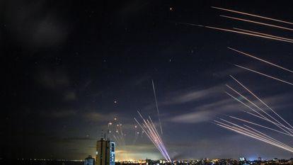 O sistema israelense de defesa antimísseis Cúpula de Ferro (à esquerda) intercepta foguetes disparados pelo Hamas, no domingo passado.