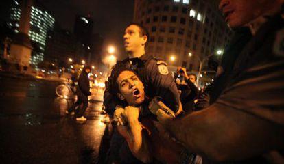 Um policial prende um manifestante terça-feira no Rio.