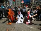 Palestinians burn pictures of U.S. President Donald Trump, Abu Dhabi Crown Prince Mohammed bin Zayed al-Nahyan and and Israeli Prime Minister Benjamin Netanyahu during a protest against the United Arab Emirates' deal with Israel, in the West Bank city of Nablus, Friday, Aug. 14, 2020.(AP Photo/Majdi Mohammed)