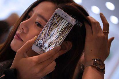 Uma mulher prova a microcâmera de um celular que permite ver o interior de seu cabelo.