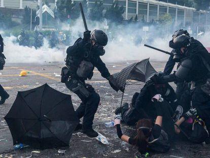 Policiais reprimem manifestantes em Hong Kong, nesta terça-feira. ISAAC LAWRENCE. No vídeo, manifestante atingido pela polícia.