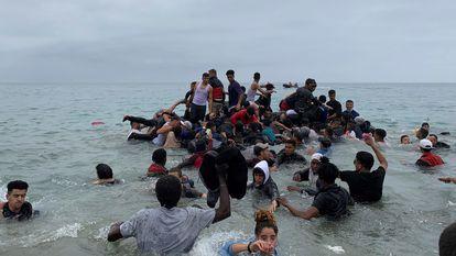 Um grupo se apropria de uma embarcação das autoridades marroquinas na praia da localidade de Fnideq para atravessar os quebra-mares de Ceuta, na terça-feira. Em vídeo, imagens das chegadas em balsas improvisadas nesta quarta.