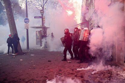 Agentes antidistúrbios em confronto com várias pessoas em uma rua do centro da capital francesa.