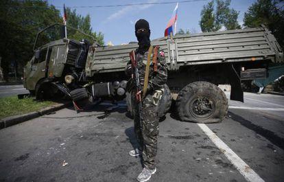 Um membro de um grupo armado pró-russo vigia uma barricada próxima a Donetsk.