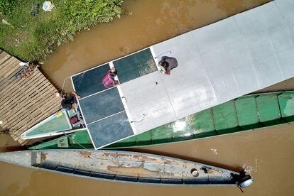 Uma equipe de técnicos indígenas instala os painéis solares no teto do novo barco, no rio Capahuari.