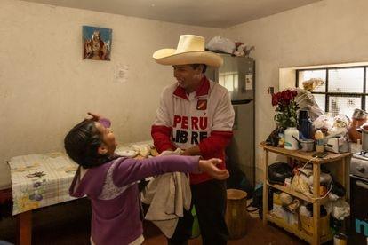 Pedro Castillo na cozinha de sua casa em Chugur, Chota, com sua filha mais nova, Alondra, de nove anos
