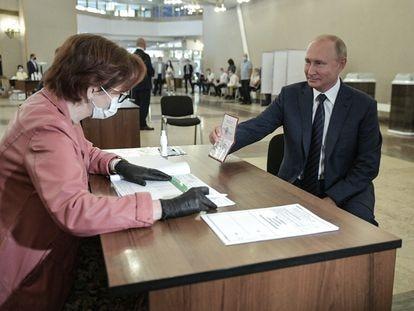 Putin mostra seu passaporte antes de votar, nesta quarta-feira, em uma seção eleitoral de Moscou.