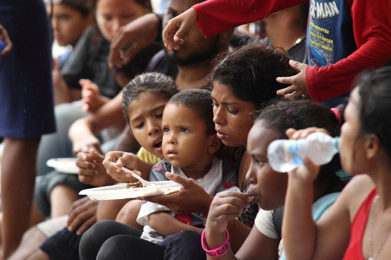 Grupo de crianças venezuelanas come depois de passar dois dias no mar, em Trinidad e Tobago, em 24 de novembro.