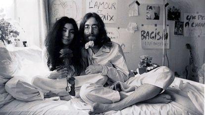 O cantor John Lennon posa de pijama na cama com sua mulher, Yoko Ono.