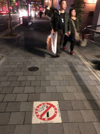 Cartaz proibindo o fumo em uma calçada do Japão.